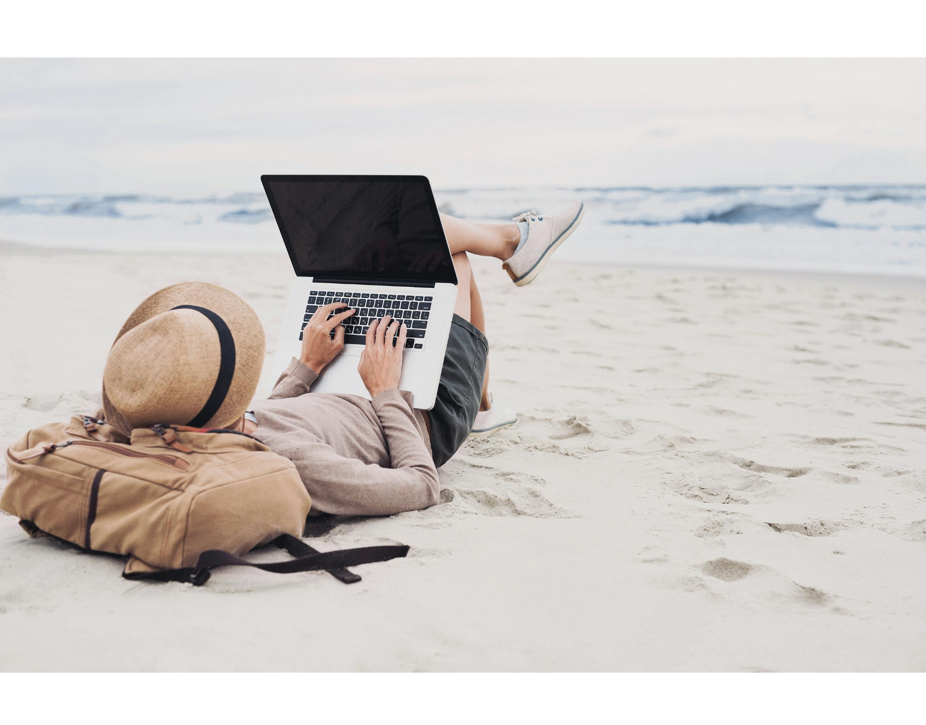 person working on laptop on beach